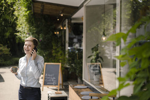 Happy businesswoman using cell phone at a cafe - KNSF06764