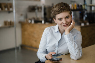Portrait of a confident woman with cell phone in a cafe - KNSF06776
