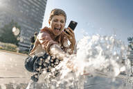Excited woman at a fountain in the city - KNSF06788