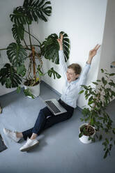 Cheering businesswoman with laptop sitting on the floor surrounded by plants - KNSF06797