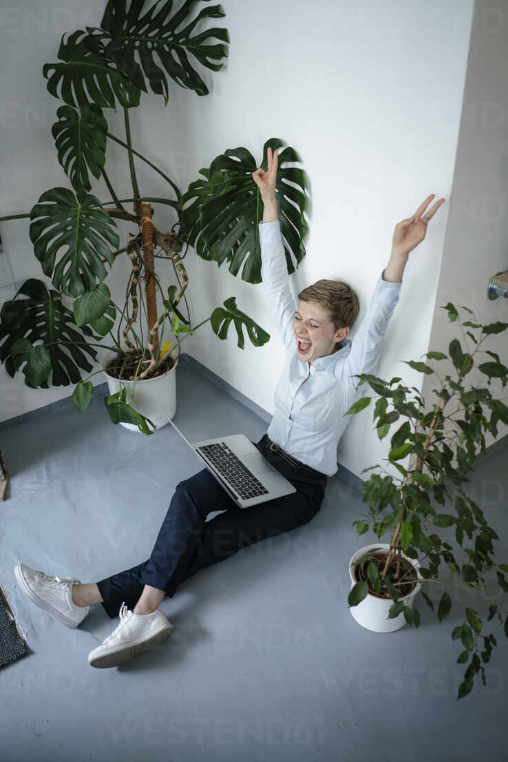 Cheering businesswoman with laptop sitting on the floor surrounded by plants - KNSF06797 - Kniel Synnatzschke/Westend61