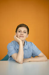 Portrait of woman leaning on table with orange background - KNSF06809