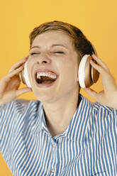 Portrait of carefree woman listening to music with orange background - KNSF06812