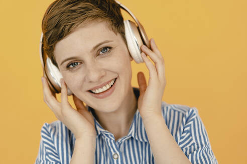 Portrait of happy woman listening to music with orange background - KNSF06815