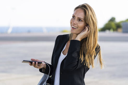 Happy businesswoman with smartphone and earphones outdoors - GIOF07183