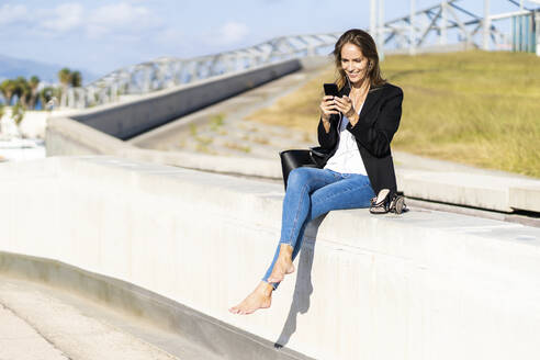 Smiling businesswoman sitting on a wall with smartphone and earphones - GIOF07186