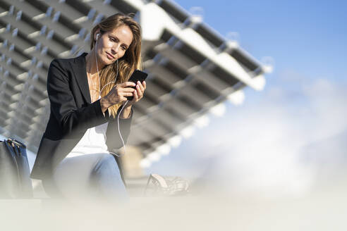 Businesswoman sitting on a wall with smartphone and earphones - GIOF07189