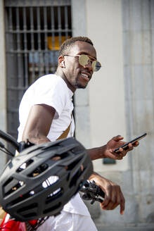Young man on his bike using his smartphone - CJMF00137