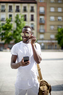 Smiling young man using smartphone and ear phones - CJMF00140