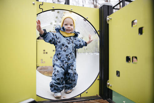 Portrait of happy toddler on playground in winter - EYAF00561