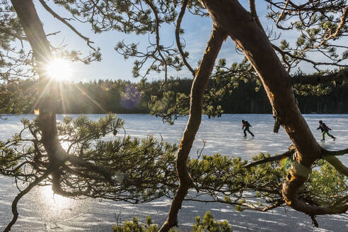 Ice skaters on frozen lake - JOHF04058