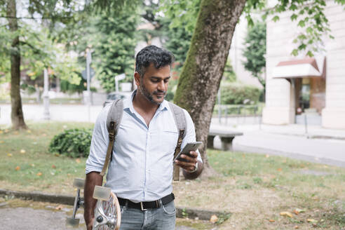Casual businessman with skateboard using smartphone in the city - ALBF01154