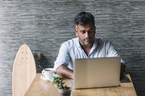 Casual businessman with skateboard using laptop in a cafe - ALBF01163