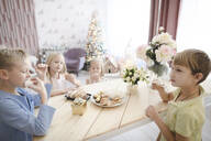 Four children eating cookies at home - EYAF00569