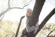Portrait of smiling little girl climbing on tree in autumn - EYAF00589
