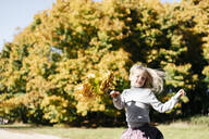 Portrait of smiling little girl running with autumn wreath in the park - EYAF00592