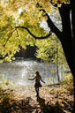 Back view of little girl enjoying autumn at riverside - EYAF00595