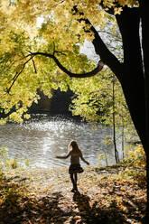 Back view of little girl enjoying autumn at riverside - EYAF00595