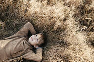 Portrait of smiling boy lying on autumnal meadow - EYAF00604