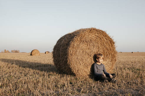 Boy sitting on stubble field leaning against hay bale - EYAF00607