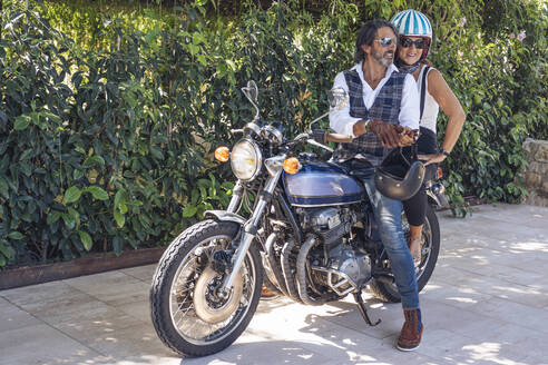 Happy mature couple on a vintage motorbike - DLTSF00249