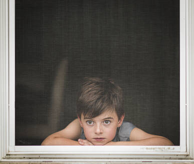 Young boy looking out through the screen of an open window. - CAVF65175