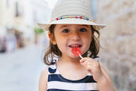 Alcúdia, Mallorca, Spain. Two year old little girl eating a heart shaped lollipop on the street - GEMF03213