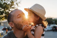 Alcúdia, Mallorca, Spain. Cute two year old little girl kissing her father on the cheek at sunset - GEMF03225