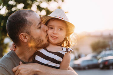 Father kissing his little daughter at sunset - GEMF03228
