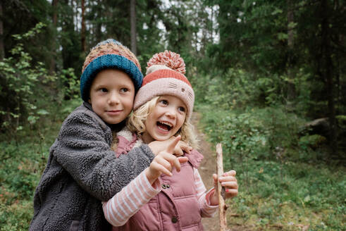 Brother hugging his sister laughing whilst walking through the forest - CAVF65334