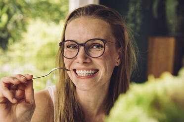 Portrait of happy young woman with glasses holding a fork - MFF04877