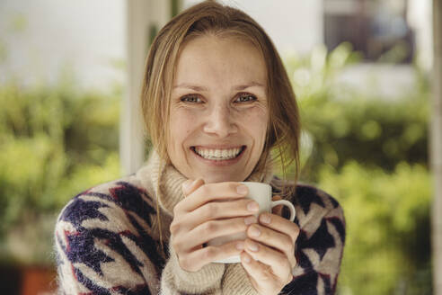 Portrait of smiling young woman wearing fluffy sweater holding a cup - MFF04883