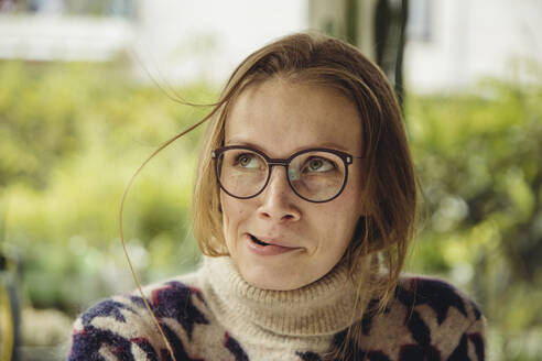 Portrait of young woman with glasses wearing fluffy sweater blowing up a strand of hair - MFF04886