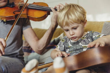 Portrait of toddler testing ukulele while his father playing violin - MFF04892