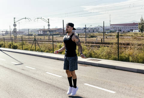 Young man skipping rope on a road - MGOF04134