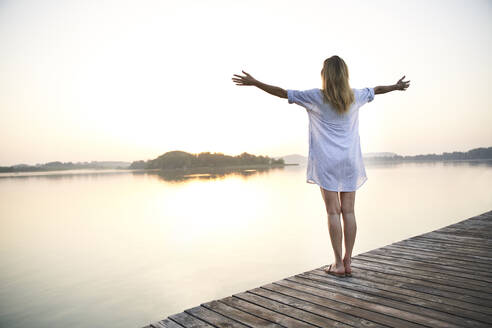 Rear view of mature woman standing on jetty at a lake at sunrise - PNEF02174