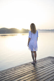 Rear view of mature woman standing on jetty at a lake at sunrise - PNEF02183
