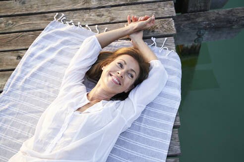 Smiling mature woman lying on a towel on a jetty at a lake - PNEF02189
