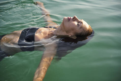 Mature woman floating in a lake with closed eyes - PNEF02207