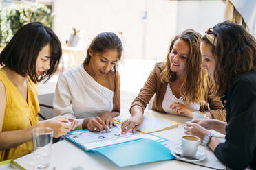Female multicultural students meeting in a cafe organizing their class schedule - MPPF00098