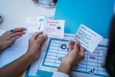 Close-up of female students organizing their class schedule and holding slips of paper - MPPF00104