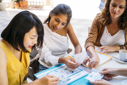 Female multicultural students meeting in a cafe organizing their class schedule - MPPF00107