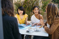Female multicultural students meeting in a cafe organizing their class schedule - MPPF00110