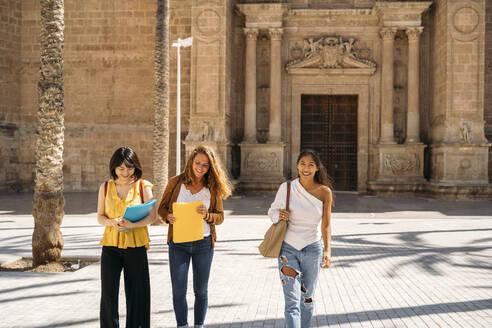 Three happy female friends walking around in the city - MPPF00113