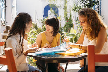Female multicultural students meeting in a cafe organizing their class schedule - MPPF00122
