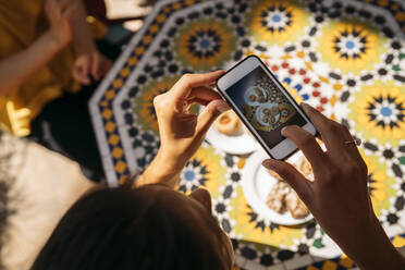 Close-up of woman taking a picture of cakes in a Moroccan cafe - MPPF00125
