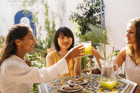 Three happy female friends meeting in a cafe clinking lemonade glasses - MPPF00128