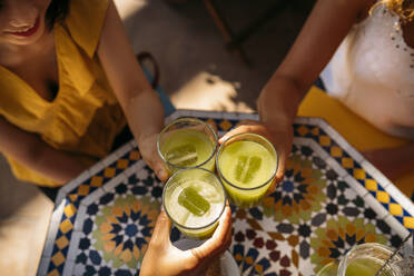 Close-up of women clinking lemonade glasses in a Moroccan cafe - MPPF00131