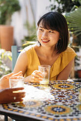 Portrait of smiling young woman with a friend at a cafe - MPPF00134