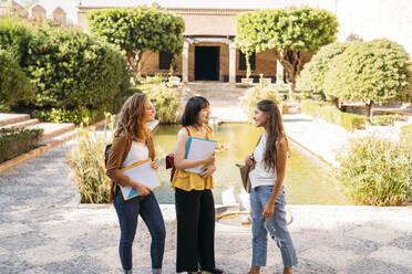 Three female friends visiting a formal garden - MPPF00146